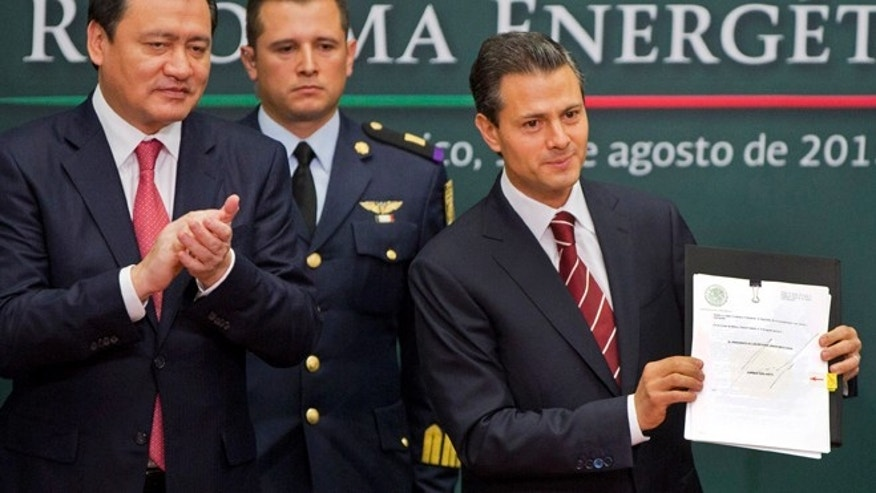 Mexico's President Enrique Pena Nieto, right, shows his proposal that would allow private firms to participate in the oil industry, on Aug.12, 2013.