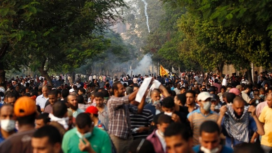 Members of the Muslim Brotherhood and supporters of ousted Egyptian President Mohamed Mursi run from tear gas released by riot police during clashes along a road at Kornish El Nile which leads to Tahrir Square during a celebration commemorating Egypt's 1973 war with Israel in Cairo October 6, 2013.