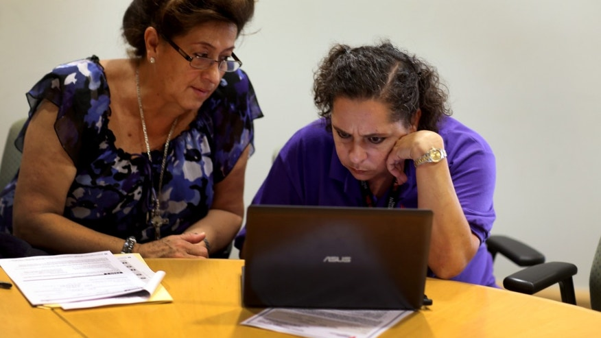 ACA navigator Nini Hadwen works with Marta Aguirre as she shops for health insurance on October 8, 2013 in Miami, Florida.