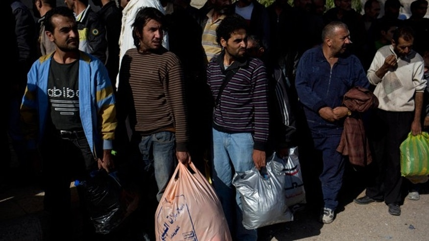 FILE --  Oct. 29, 2013: Men wait to be searched by the Syrian military after they have crossed from the rebel held suburb of Moadamiyeh to the government held territory in Damascus, Syria.