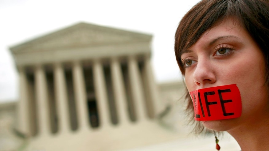 "WASHINGTON - OCTOBER 06:  Anti-abortion demonstrator Belinda Yoder, 20, of Charlotte, North Carolina, stands in front of the Supreme Court on the first day of the court's new term October 6, 2008 in Washington, DC. About 20 demostrators gathered at the court to mark ""Pro-Life Memorial Day 2008,"" an event sponsored by American Life League and several other organization.  (Photo by Chip Somodevilla/Getty Images)"