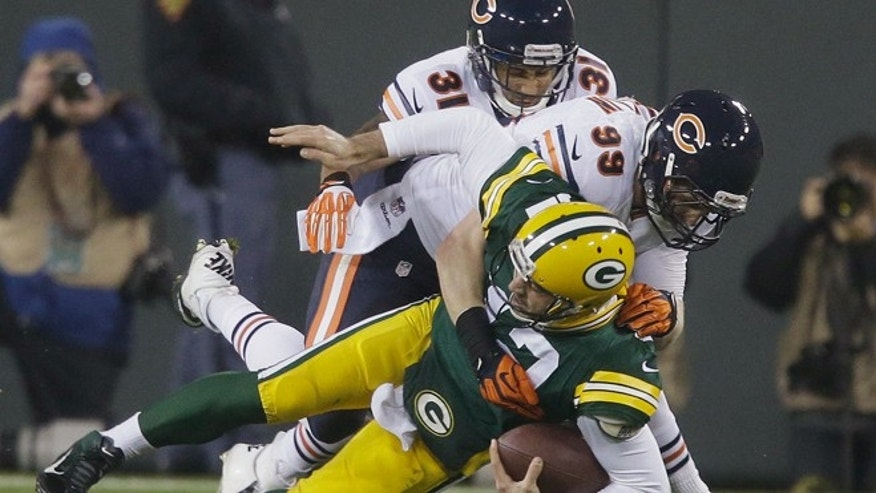 FILE -- Nov. 4, 2013: Green Bay Packers quarterback Aaron Rodgers is sacked by Chicago Bears' Shea McClellin (99) and Isaiah Frey (31) during the first half of an NFL football game in Green Bay, Wis. Rodgers left the game after the play.