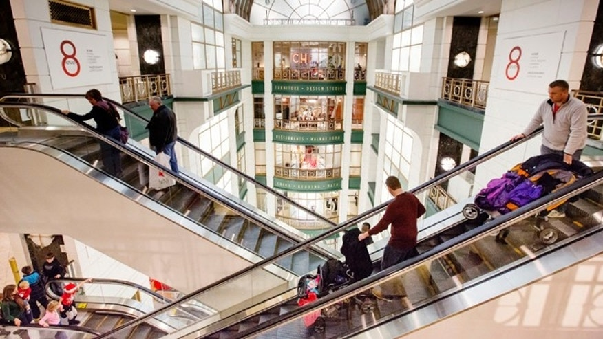 Shoppers ride escalators between floors during Black Friday shopping at Macy's on Friday, Nov. 29, 2013, in Chicago.