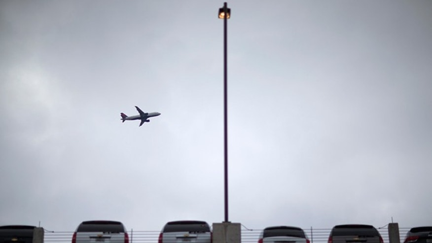 Nov. 27, 2013: An airplane takes off as rental cars sit parked at the car rental center at Hartsfield-Jackson Airport in Atlanta.