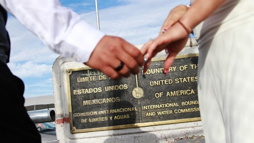 U.S. citizen Edgar Falcon, left, and Maricruz Valtierra of Mexico, hold hands at the U.S.-Mexico border where they were married, Tuesday, Aug. 27, 2013 in El Paso, Texas. Like many other couples made up of a US citizen and a foreigner, Falcon and Valtierra, who has been declared inadmissible after an immigration law violation, hope immigration reform will help them live together in the U.S. (AP Photo/Juan Carlos Llorca)
