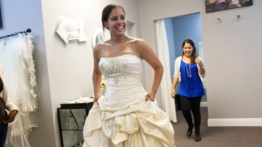 "Nov. 13, 2013: Vanessa Gathers of Tampa tries on a dress during the ""Operation Wedding Gown"" event at The White Closet Bridal in Tampa. Gathers who is in the Air Force and her fiance in the Army will be getting married in December. Military wives who qualified we able to come and receive free wedding dresses. The bride or their spouse had to currently be serving in the military, be currently deployed, have a future deployment or deployed within the last 5 years. The event was a part of the Bride's Across America's campaign, ""Operation Wedding Gown"". The organization has donated over 10, 000 wedding gowns to military brides."