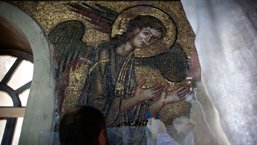 FILE -- Dec. 10, 2013. A restoration expert works on a mosaic inside the Church of the Nativity in the West Bank city of Bethlehem.