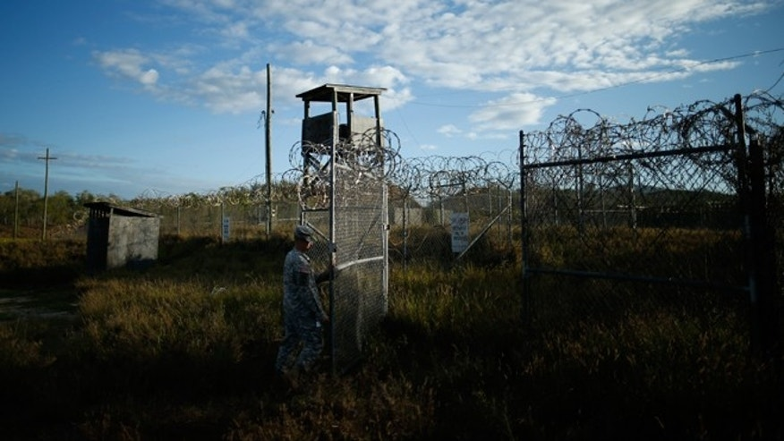 FILE -- Nov. 21, 2013: In this photo reviewed by the U.S. military, a soldier closes the gate at the now abandoned Camp X-Ray, which was used as the first detention facility for al-Qaida and Taliban militants who were captured after the Sept. 11 attacks at Guantanamo Bay Naval Base, Cuba.