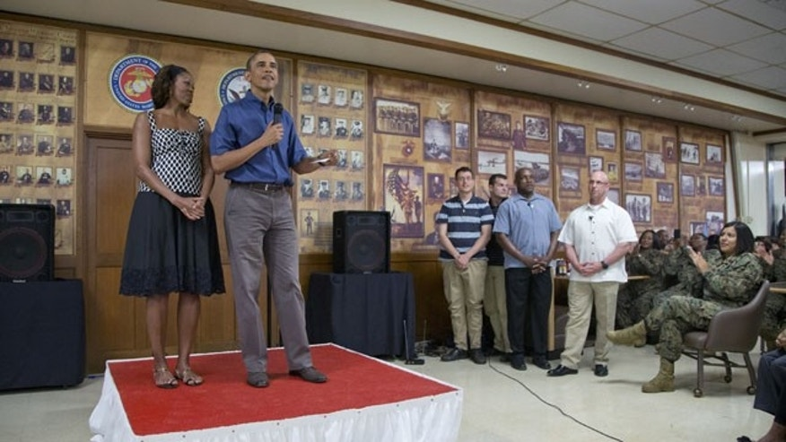 December 25, 2013: President Barack Obama and first lady Michelle Obama speak to members of the military and their families in Anderson Hall at Marine Corps Base Hawaii in Kaneohe Bay. (AP Photo)