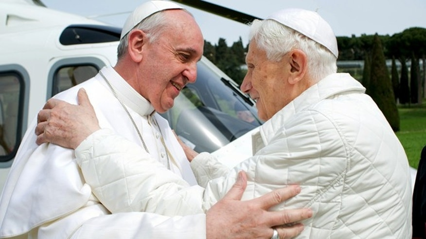 FILE -- Pope Francis greets Pope Emeritus Benedict XVI.