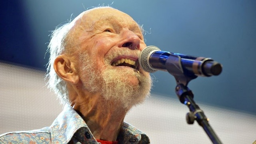 FILE -- Sept. 21, 2013: Pete Seeger performs on stage during the Farm Aid 2013 concert at Saratoga Performing Arts Center in Saratoga Springs, N.Y.
