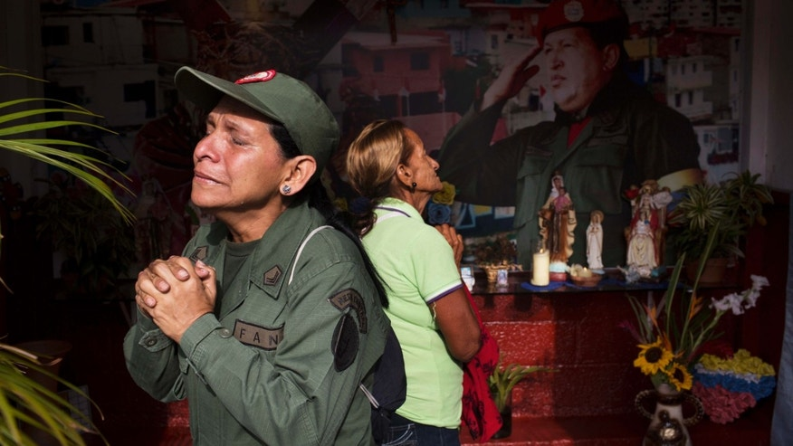 Marisol Perez, Venezuelan Army specialist, cries while visiting a chapel near Venezuela's late President Hugo Chavez's mausoleum in Caracas, Venezuela, Wednesday, March 5, 2014. Wednesday's anniversary of Chavez's death follows weeks of sometimes violent protests that the government says have left 18 dead. To mark Chavez's passing, who died  March 5, 2013 at the age of 58, President Nicolas Maduro has decreed a 10-day-long commemoration. (AP Photo/Rodrigo Abd)