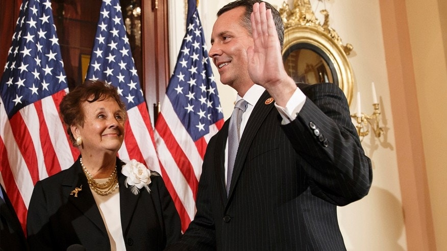 Newly elected Republican Rep. David Jolly of Florida, right, poses for a ceremonial swearing-in with his mother Judy Jolly and House Speaker John Boehner of Ohio, on  Capitol Hill in Washington, Thursday, March 13, 2014.