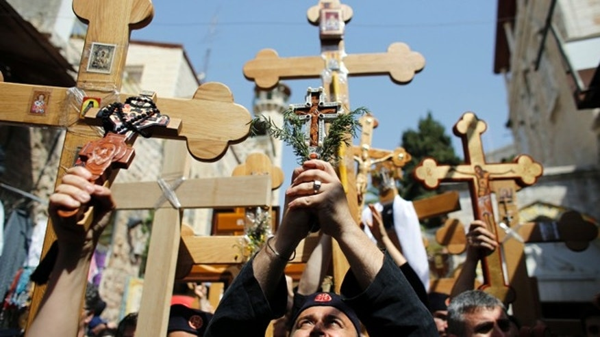 Orthodox Christian worshippers hold crosses as they take part in the Eastern and Orthodox Church's Good Friday procession along the Via Dolorosa in Jerusalem's Old City.