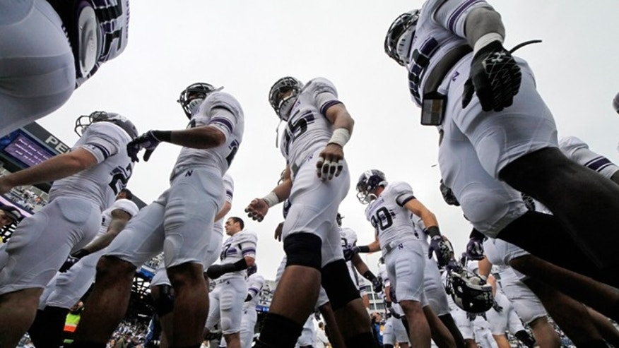 FILE - Oct 6, 2012:  Tthe Northwestern football team heads to the locker room after warming up before an NCAA college football game against Penn State in State College, Pa. A ruling Wednesday, March 26, 2014, that the Northwestern football team can bargain with the school as employees represented by a union may not by itself change the way amateur sports operate. But it figures to put more pressure on the NCAA and the major conferences to give something back to the players to justify the billions of dollars the players bring in -- and never see.