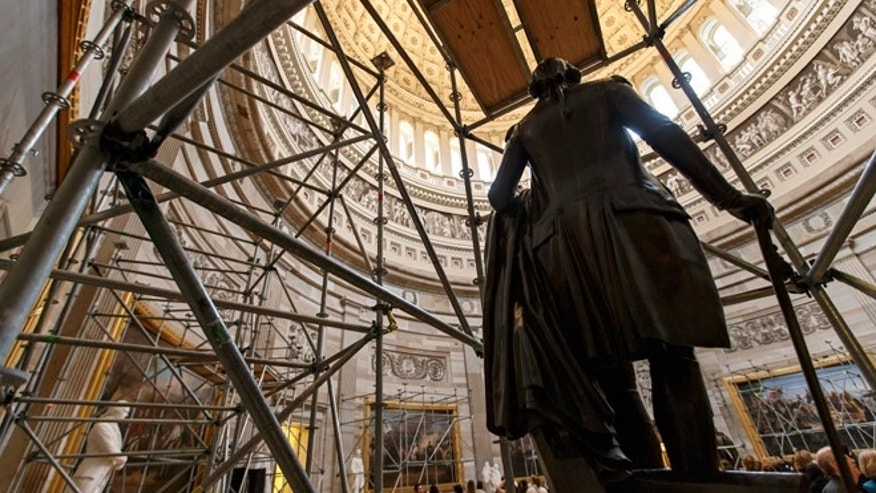 FILE -- April 7, 2014: With the statue of George Washington in the foreground, scaffolding begins to rise in the Rotunda of the U.S. Capitol in preparation for a multi-year project to repair the dome that has more than 1,000 cracks and deficiencies, in Washington, D.C.