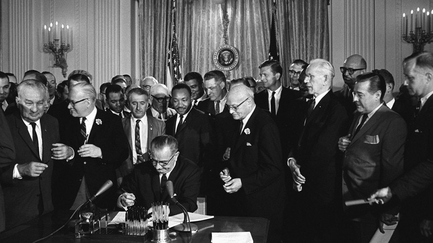 U.S President Lyndon Johnson signs the Civil Rights Act of 1964 as Martin Luther King Jr. and others watch in the White House East Room, Washington, D.C.