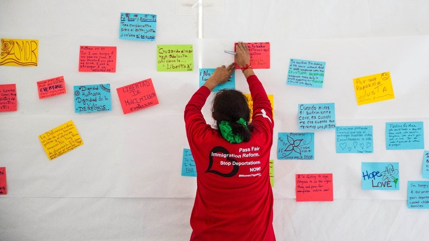 WASHINGTON, DC - APRIL 7: Antonia Surco, of Silver Spring, Maryland, hangs hand-written messages  about fasting for immigration reform on the wall of a tent on the National Mall, during the 'Women's Fast For Families' event, April 7, 2014 in Washington, DC. According to organizers, around 100 women signed up to fast for 48 hours on the National Mall to call for 'fair immigration reform and an end to deportations.' (Drew Angerer/Getty Images)