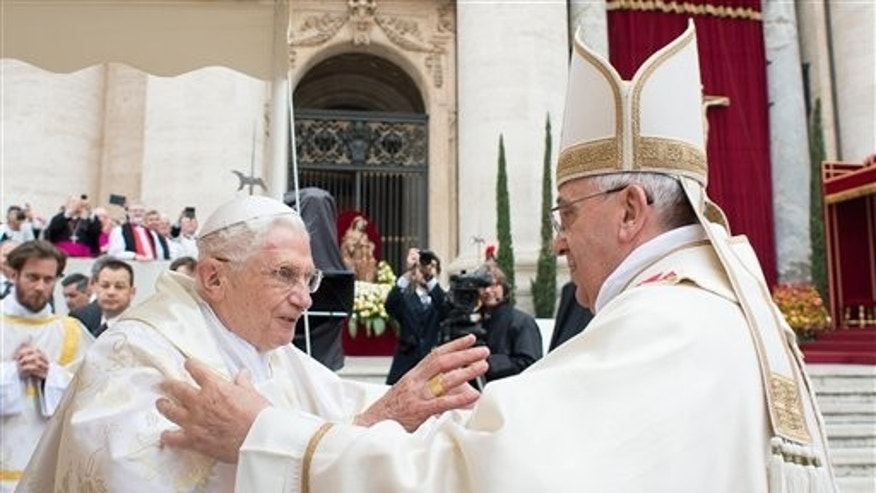 April 27, 2014: In this photo provided by the Vatican newspaper L'Osservatore Romano, Pope Francis, right, embraces his predecessor Pope Emeritus Benedict XVI, during a ceremony in St. Peter's Square at the Vatican.