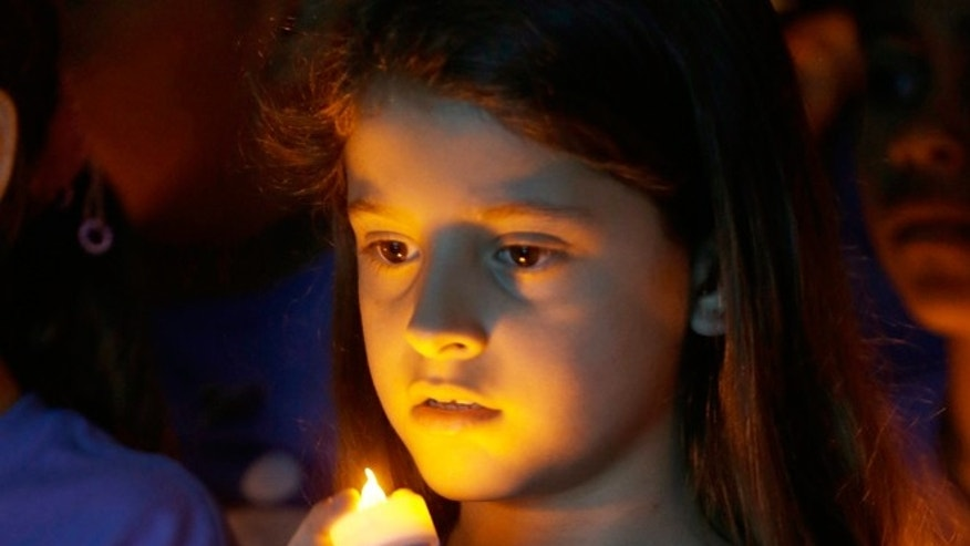 FILE -- April 23, 2014: Melanie Mamondes, 8, participates in a candlelight vigil commemorating National Child Abuse Prevention Month at Jose Marti Park in Miami. Amigos For Kids, a nonprofit organization dedicated to preventing child abuse and neglect, held the event attended by about 200 kids and their families.
