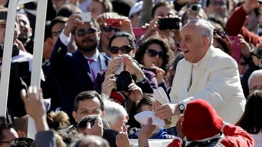 April 16, 2014: Pope Francis exchanges a skull cap with a participant in the audience as he tours with his pope mobile St. Peter's Square at the Vatican.