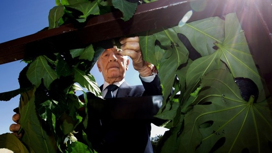FILE -- April 28, 2014: Israel's President Shimon Peres lays a wreath during the annual Holocaust Remembrance Day ceremony, at the Yad Vashem memorial in Jerusalem.