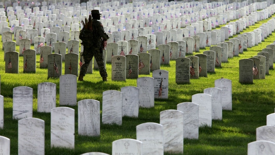 Army 1st Sargeant Shelly Jenkins places flags on graves at Arlington National Cemetery ahead of Memorial Day.