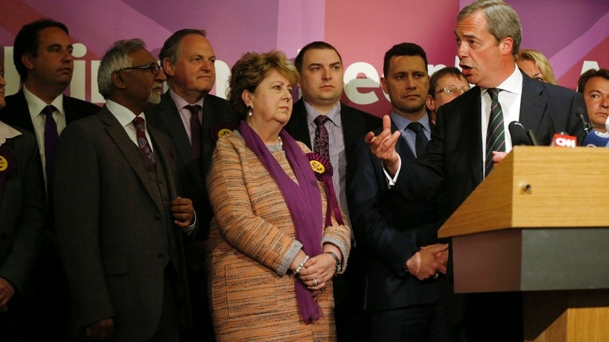 Surrounded by the newly elected UKIP MEPs, Nigel Farage, leader of UK Independence Party and newly re-elected MEP, right, speaks to the media during a post European Elections press conference in central London, Monday, May 26, 2014.