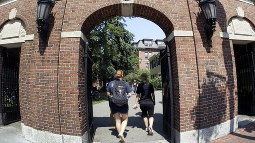 Pedestrians walk through a gate on the campus of Harvard University in Cambridge, Mass.