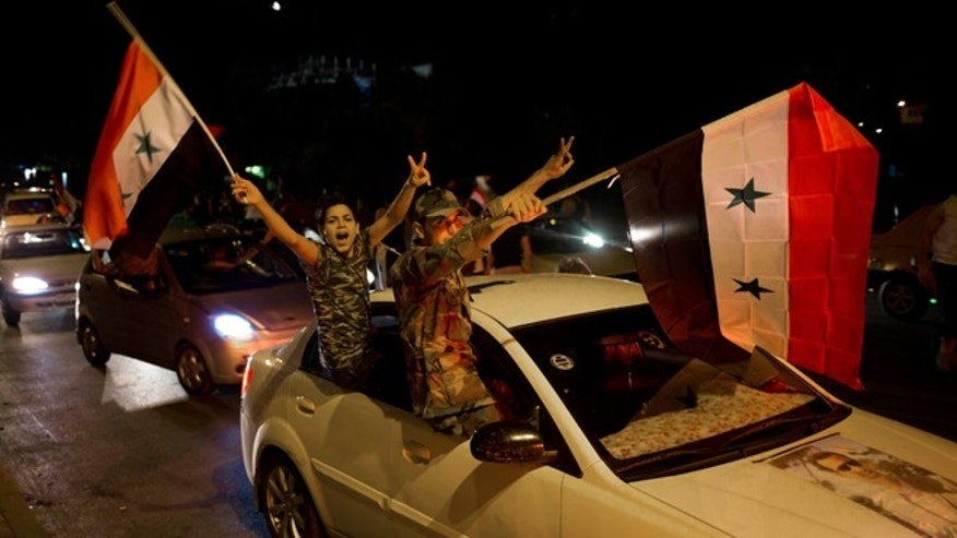 Syrian soldiers celebrate Bashar Assad's presidential re-election in Damascus, Syria, Wednesday June 4, 2014. Assad has been re-elected in a landslide, officials said Wednesday, capturing another seven-year term in the middle of a bloody 3-year-old uprising against his rule that has devastated the country.