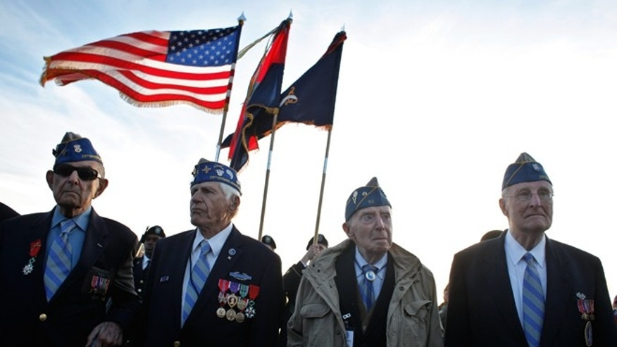 June 6, 2014: From left, World War II veterans of the U.S. 29th Infantry Division, Hal Baumgarten, 90 from Pennsylvania, Steve Melnikoff, 94, from Maryland, Don McCarthy, 90 from Rhode Island, and Morley Piper, 90, from Massachusetts, attend a D-Day commemoration, on Omaha Beach, western France.