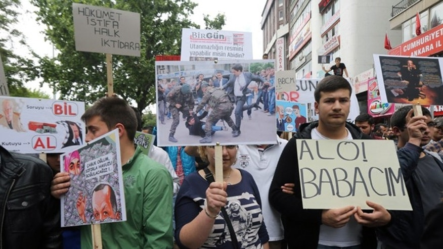 June 7, 2014: Members of Turkey's main opposition Republican People's Party hold a placard with an image of prime minister's advisor Yusuf Yerkel kicking a miner in Soma, as they protest against corruption by the Prime Minister Recep Tayyip Erdogan and his government, in Ankara, Turkey. Caption reads: 'Hello my father' at right and 'government, resign!'