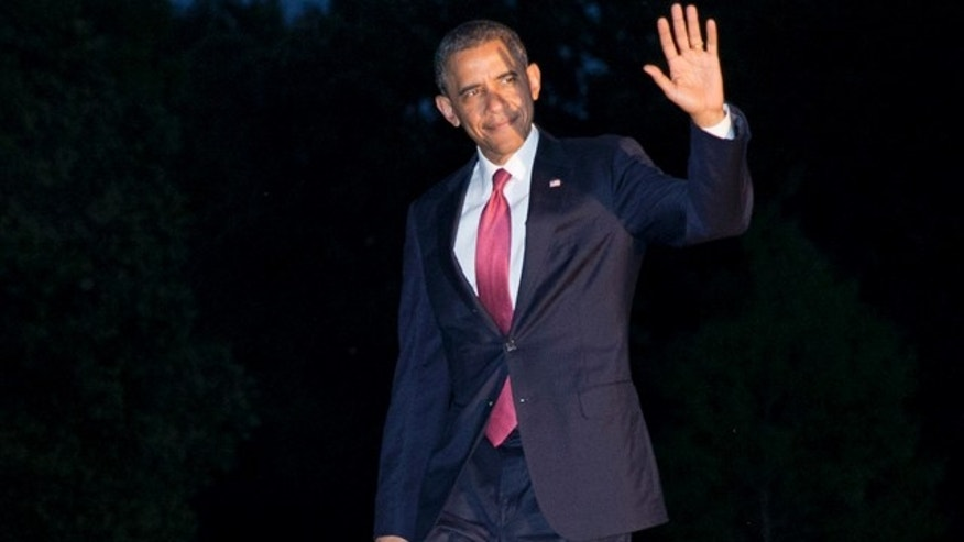 June 6, 2014: President Barack Obama waves to the media as he returns at dusk on the South Lawn of the White House in Washington after attending remembrance activities on the 70th anniversary of D-Day in Normandy, France. (AP Photo/Jacquelyn Martin)