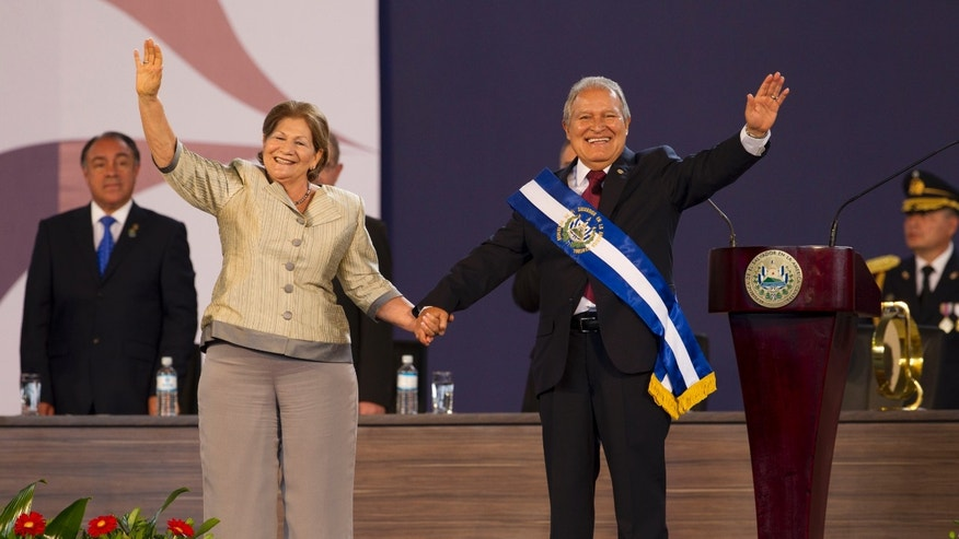 In this June 1, 2014, photo, El Salvador's incoming President, Salvador Sanchez Ceren, right, and his wife Margarita Villalta wave during his swearing in ceremony in San Salvador, El Salvador. (AP Photo/Moises Castillo)