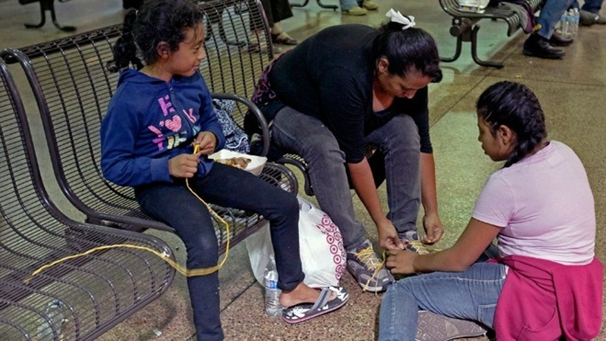 FILE -- May 29, 2014: Elana Carmen, middle, with her daughters Abigail, right, and Ayala, of El Salvador, tie their shoes with yellow rope for shoe laces,  at the Greyhound bus terminal in Phoenix. About 400 mostly Central American women and children caught crossing from Mexico into south Texas were flown to Arizona after border agents there ran out of space and resources. Officials then dropped hundreds of them off at Phoenix and Tucson Greyhound stations, overwhelming the stations and humanitarian groups who were trying to help.