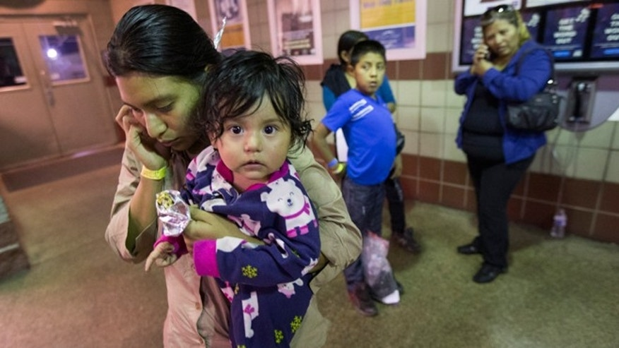 May 28, 2014: Judy Elizabeth Martinez, holding Marjorie, tries to reach family after being released by ICE at a Greyhound Bus station in Phoenix. She is from Guatemala and was flown from Georgia to Arizona by ICE. The Border Patrol says about 400 migrants were flown from Texas to Arizona because of a surge in migrants being apprehended in Texas.