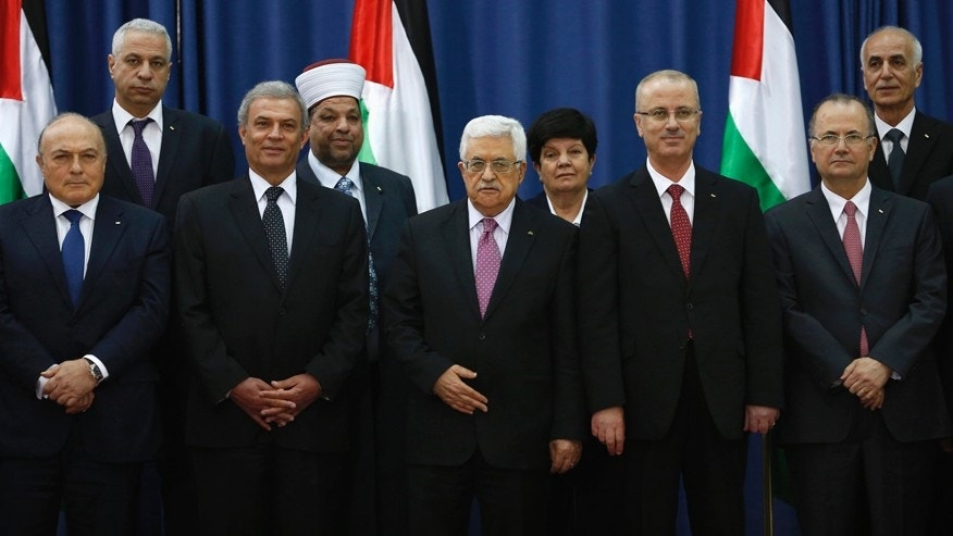 Palestinian Prime Minister Rami Hamdallah (4th L) and Palestinian President Mahmoud Abbas (3rd L) pose for a group photo with Palestinian ministers during a swearing-in ceremony of the unity government, in the West Bank city of Ramallah June 2, 2014.