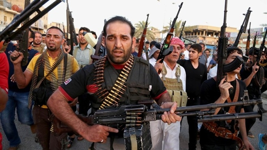 June 13, 2014: Iraqi Shiite tribal fighters deploy with their weapons while chanting slogans against the Al Qaeda-inspired Islamic State of Iraq and the Levant (ISIS), to help the military, which defends the capital in Baghdad's Sadr City, Iraq.