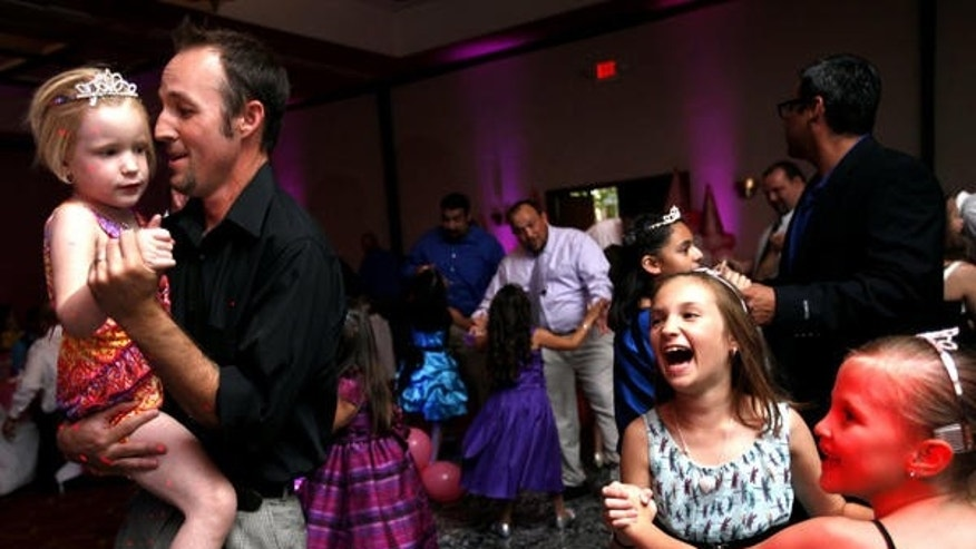 June 14, 2014: Dustin Moon dances with his daughter Madi Moon in his arms while Baylee Moon shares a dance with Madison Jerome during the first annual Daddy Daughter Dance on Saturday in Odessa, Texas.
