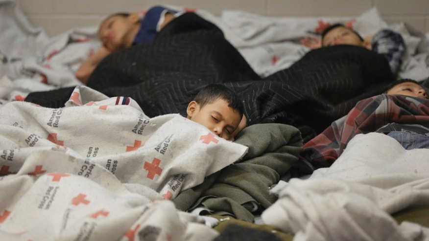 Kids sleep in a holding cell at a U.S. Customs and Border Protection facility, June 18, 2014, in Brownsville,Texas.