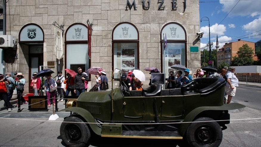 "Tourists gather on Friday, June 27, 2014, around replica of the ""Graf & Stift"" car that Archduke Franz Ferdinand and his wife Sofia rode in as it is parked in front of museum at the historical street corner in downtown Sarajevo, where Gavrilo Princip, assassinated Austro-Hungarian heir to the throne Archduke Franz Ferdinand and his wife Sofia, on June 28, 1914. The assassination was the event that ignited the start of World War One."