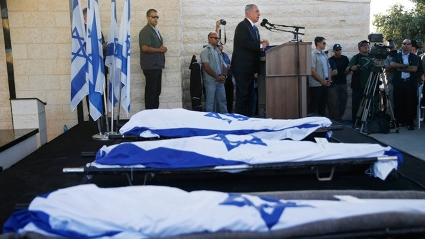 July 1, 2014: Israeli Prime Minister Benjamin Netanyahu eulogizes three Israeli teens who were abducted and killed in the West Bank during their joint funeral in the Israeli city of Modiin, Tens of thousands of mourners converged Tuesday in central Israel for the funeral service for three teenagers found dead in the West Bank after a two week search and crackdown on the Hamas militant group, which Israeli leaders have accused of abducting and killing the young men. The deaths of Eyal Yifrah, 19, Gilad Shaar, 16, and Naftali Fraenkel, a 16-year-old with dual Israeli-American citizenship, have prompted angry calls for revenge and Prime Minister Benjamin Netanyahu convened his security Cabinet for an emergency meeting to discuss a response to the killings, hours after airstrikes targeted dozens of suspected Hamas positions in the Gaza Strip.