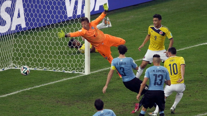 FILE - In this June 28, 2014, file photo, Colombia's James Rodriguez, right, scores his side's second goal past Uruguay's goalkeeper Fernando Muslera during the World Cup round of 16 soccer match between Colombia and Uruguay at the Maracana Stadium in Rio de Janeiro, Brazil. This Colombian team's unselfish poise and muscular grace has let people ''transcend the political tribalism'' that has defined Colombia's violent history.  (AP Photo/Themba Hadebe, File)