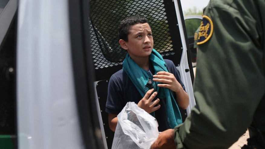 A U.S. Border Patrol agent prepares to take an unaccompanied Salvadorian minor, 13, to a processing center after he crossed the Rio Grande on July 24, 2014 in Mission, Texas.
