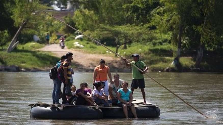 In this July 11, 2014, photo, people are rafted to the Mexican shore, across the Suchiate river that separates Tecun Uman, Guatemala and Ciudad Hidalgo, Mexico, on a makeshift raft.  (AP Photo/Eduardo Verdugo)