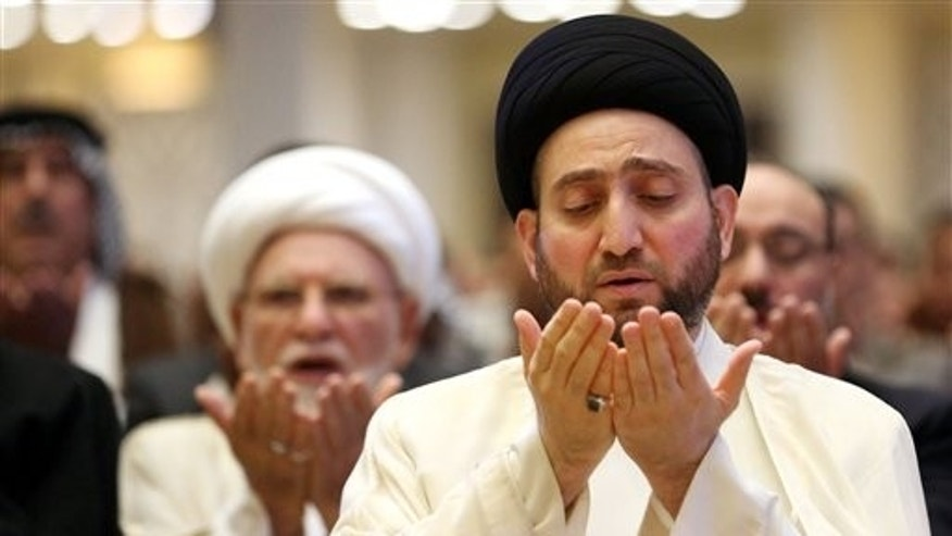 Ammar al-Hakim, right, the leader of the Supreme Islamic Council of Iraq, take part in the Eid al-Fitr prayer in Baghdad, Iraq, Tuesday, July 29, 2014. The Eid al-Fitr holiday marks the end of the holy fasting month of Ramadan. (AP Photo/Hadi Mizban)