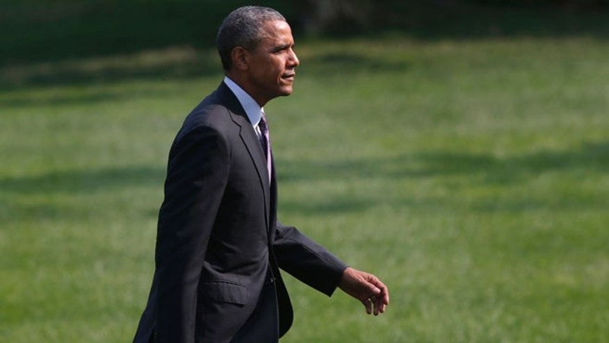 President Barack Obama walks on the South Lawn of the White House in Washington, Wednesday, July 30, 2014.
