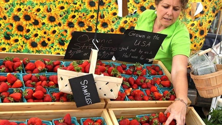 FILE -- Lisa Steketee restocks strawberries during the Laramie Farmers Market in Wyoming.