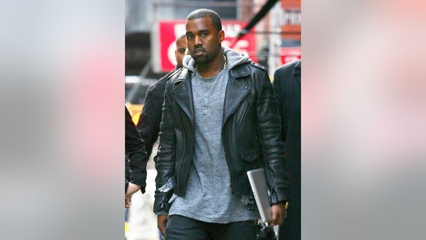 Kanye West leaves hotel with an ipad under his arm on December 1, 2011 X17online.com EXCLUSIVE