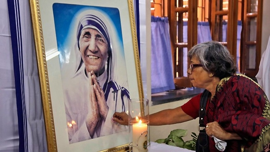 Sept. 5, 2014: An Indian Catholic woman offers prayers as she touches a portrait of Mother Teresa on her 17th death anniversary at the Missionaries of Charity in Kolkata, India.
